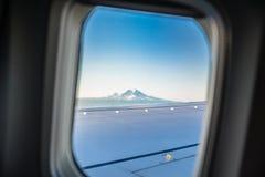 Airplane window, view of Mount Rainier stock photography