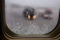 Airplane window with view partially blocked by falling snow. Blurred deicing trucks on the tarmac. Royalty Free Stock Images