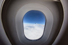 Airplane window with wing and cloudy sky behind. Royalty Free Stock Image