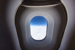 Airplane window with wing and cloudy sky behind. Royalty Free Stock Photos