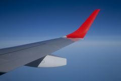Airplane wing. View of an airplane wing with red mark in the sky royalty free stock photos