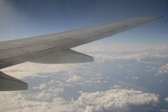 Airplane Wing. Against blue sky background with clouds Stock Photo