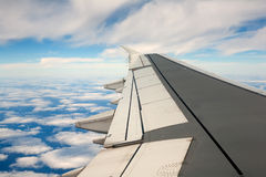 Airplane wing. In the blue sky with white clouds royalty free stock photos
