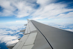 Airplane wing. In the blue sky with white clouds royalty free stock photo