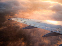 Airplane wing. In dramatic sunset clouds Stock Photo