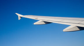 Airplane wing. View from inside of airplane window looking at airplane wing Royalty Free Stock Image