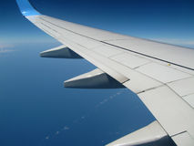 Airplane Wing. View over the ocean on a perfect blue sky background Stock Images