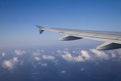 Airplane wing. View from inside of airplane window looking at airplane wing and clouds Royalty Free Stock Photos