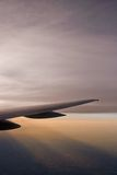Airplane Wing. And flaps over a brilliant sky at twilight while flying on an airline royalty free stock photography