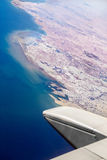 Airplane wing. Aerial shot of blue sky and ocean from inside of airplane flying to HongKong Stock Images