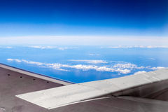 Airplane wing. Aerial shot of blue sky and ocean from inside of airplane flying to HongKong Royalty Free Stock Photo