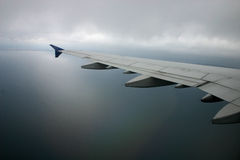 Airplane wing. Ovwr the water in the fog Stock Photography