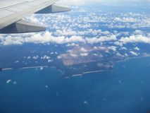 The airplane wing above the blue ocean. Before landing, view from the airplane`s window Royalty Free Stock Photo