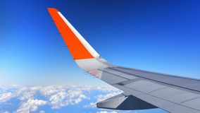 Airplane wing above cloud and blue sky. Airplane wing on cloudscape on blue sky Royalty Free Stock Images