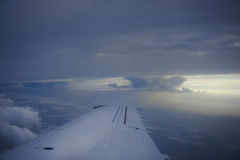 An airplane wing above the clouds Stock Photo