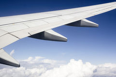 Airplane wing above the clouds Stock Photography
