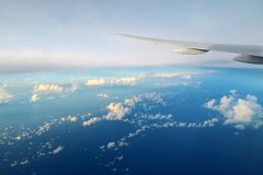 Airplane wing above the clouds in evening light Stock Images