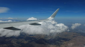 Airplane wing above the clouds and mountains Royalty Free Stock Image
