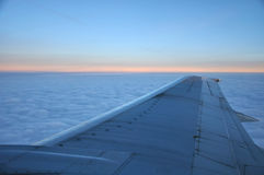 Airplane wing above morning clouds and sunrise Royalty Free Stock Images