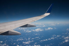 Airplane wing above the ocean blue Stock Photography