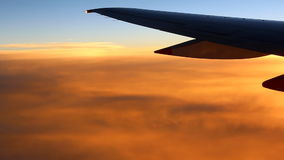 Airplane wing above orange clouds stock video footage