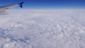 Airplane wing aerial window clouds sunlight 4k. Wing of aircraft on the background of clouds and blue sky stock footage