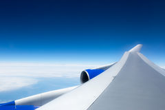 Airplane wing against blue sky from the porthole Royalty Free Stock Image