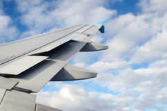 Airplane wing against clouds in a blue sky Stock Image