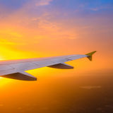 Airplane wing against a sunrise sky Stock Photo