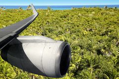 Airplane wing aircraft turbine flying. Over palm trre mangrove jungle Stock Images