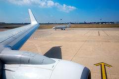 Airplane wing in airport with aircraft background. With blue sky Stock Image