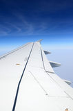 Airplane wing on a background of sky and clouds Stock Image