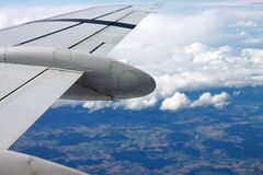 Airplane wing in blue skies