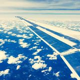 Airplane wing in blue skies. Airplane wing over blue skies and clouds Royalty Free Stock Images