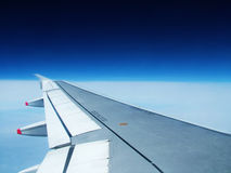 Airplane wing and blue sky. Airplane wing with flaps, blue sky and dark outer space Stock Photography