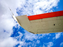 Airplane wing on blue sky from below Stock Photo