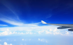 Airplane wing in blue sky with cloudy below Stock Photos