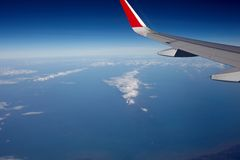 Airplane wing and blue sky. Airplane wing with flaps, blue sky and dark outer space Stock Images
