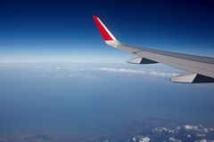 Airplane wing and blue sky. Airplane wing with flaps, blue sky and dark outer space Royalty Free Stock Photos
