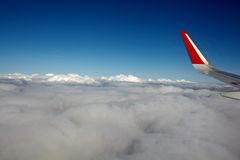 Airplane wing and blue sky. Airplane wing with flaps, blue sky and dark outer space Royalty Free Stock Photo