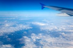 Airplane Wing in the Blue sky. View from a plane window Royalty Free Stock Photo