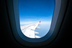 Airplane wing on blue sky, view through plane window, with copy space Royalty Free Stock Image