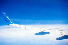 Airplane wing with blue sky and white clouds Stock Photography