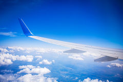 Airplane wing with blue sky and white clouds Royalty Free Stock Images