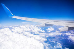 Airplane wing with blue sky and white clouds Stock Photo