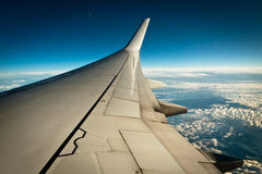 Airplane wing with clouds royalty free stock photo