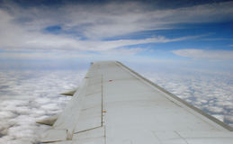 Airplane wing and cloudscape. View of modern airplane wing in flight with cloudscape background Royalty Free Stock Photography