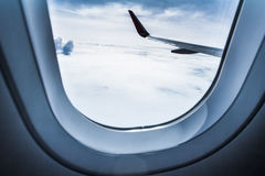 Airplane wing and cloudscape seen through airplane window Royalty Free Stock Image