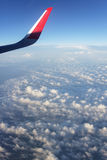 Airplane wing at cloudy sky. Travel Stock Image