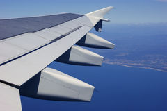 Airplane wing and coastline Stock Photos